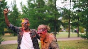 Dos individuos barbudos con las caras coloridas cubiertas con la pintura están bailando en césped en el parque que salta y que so metrajes