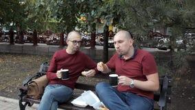 Dos individuos calvos de los jóvenes en la cena se están sentando en un parque que comen los bocadillos y que beben el café, char almacen de metraje de vídeo