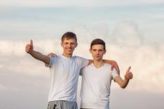 Dos individuos del hermano se oponen al cielo feliz fotografía de archivo