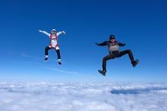 Dos individuos divertidos se están cayendo sobre las nubes blancas fotos de archivo