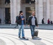 Dos individuos están caminando a través de las calles de Génova, Italia y están mirando alrededor, hablando el uno al otro Foto de archivo libre de regalías
