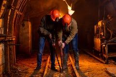 Dos individuos jovenes en un uniforme de trabajo y cascos protectores, realizan el trabajo en la mina imagenes de archivo