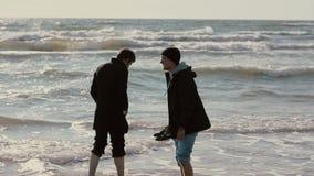 Dos individuos jovenes están empapando sus pies en las ondas del mar que sonríen y que hablan el uno al otro almacen de video