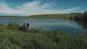 Dos individuos jovenes están pescando en el lago almacen de video