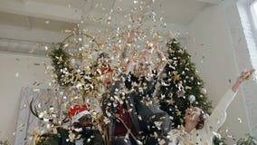 Dos individuos jovenes hermosos que llevan en los sombreros de Papá Noel con sus novias lanzan confeti de oro en la celebración e almacen de metraje de vídeo