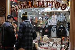 Dos individuos que miran un escaparate de un tatuaje hacen compras Imagen de archivo libre de regalías