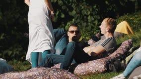 Dos individuos que ponen en las almohadas afuera en la hierba, muchachas en el vestido blanco entran  almacen de metraje de vídeo