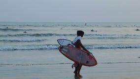 Dos individuos una persona que practica surf que camina en la playa en la puesta del sol almacen de metraje de vídeo