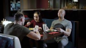 Dos individuos y la muchacha bonita están pasando tiempo en un restaurante por la tarde, están hablando alegre y están disfrutand almacen de video