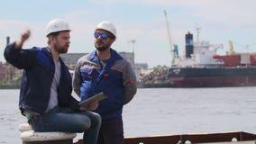 Dos ingenieros con el ordenador portátil comunican en puerto del buque mercante almacen de metraje de vídeo