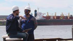 Dos ingenieros con el ordenador portátil sonríen y comunican en puerto del buque mercante almacen de metraje de vídeo