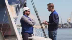 Dos ingenieros con el ordenador portátil sonríen y comunican y sacuden las manos en puerto del buque mercante almacen de video