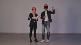 Dos ingenieros de construcción en cascos con las gafas de VR que manejan proyecto de edificio en 3d Fotos de archivo libres de regalías