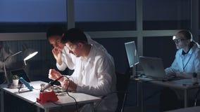 Dos ingenieros de la raza mixta que comprueban la placa madre con el probador del multímetro almacen de metraje de vídeo