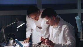 Dos ingenieros electrónicos de la raza mixta que trabajan con el probador del multímetro y otros dispositivos electrónicos almacen de metraje de vídeo