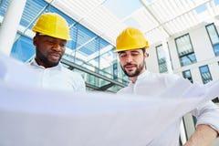 Dos ingenieros en el planeamiento de la construcción foto de archivo