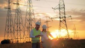 Dos ingenieros en trabajo uniforme cerca de líneas eléctricas Fondo de la puesta del sol metrajes