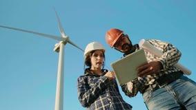 Dos ingenieros en un campo están discutiendo mientras que miran la tableta El generador de viento está en el fondo lento almacen de video