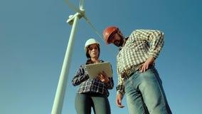 Dos ingenieros en un campo piensan en la información de la tableta, sugiriendo soluciones posibles El generador de viento está pr almacen de video