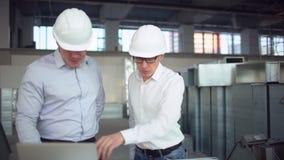 Dos ingenieros están trabajando en un equipo de escritorio en una fábrica Tubos de aire para condicionar y ventilación y fuego metrajes