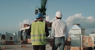 Dos ingenieros jovenes que caminan a través del emplazamiento de la obra, grúa grande del fondo, ellos equipo de seguridad que ll metrajes