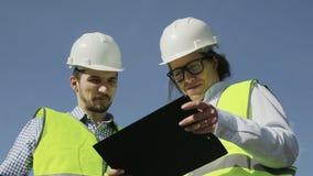 Dos ingenieros jovenes un hombre y una mujer en chalecos y cascos verdes almacen de video