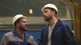 Dos ingenieros miran para arriba y discuten en fábrica de la industria pesada almacen de metraje de vídeo