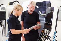 Dos ingenieros que actúan la maquinaria del CNC en piso de la fábrica Imagenes de archivo