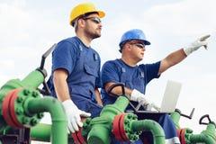 Dos ingenieros que trabajan dentro de refinería del petróleo y gas imágenes de archivo libres de regalías