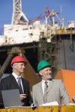 Dos inspectores de la plataforma petrolera con una computadora portátil Fotografía de archivo libre de regalías