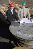 Dos inspectores de la plataforma petrolera con una computadora portátil Foto de archivo libre de regalías
