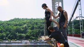 Dos instructores preparan a la muchacha para un salto almacen de video