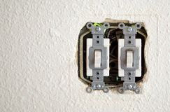 Dos interruptores de la luz con el cableado expuesto en una pared imagen de archivo libre de regalías