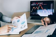 Dos inversores están trabajando así como analizar los gráficos comunes de los datos en el papel y la visión de los datos sobre la imagenes de archivo