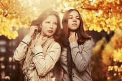 Dos jóvenes forman a las muchachas adolescentes que caminan en parque del otoño Imagenes de archivo