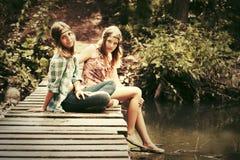 Dos jóvenes forman a muchachas adolescentes en un bosque del verano Imagenes de archivo