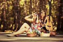 Dos jóvenes forman a muchachas con la guitarra en un bosque del verano Foto de archivo
