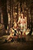 Dos jóvenes forman a muchachas con la guitarra en un bosque del verano Imágenes de archivo libres de regalías