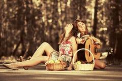 Dos jóvenes forman a muchachas con las cestas de fruta en bosque del verano Imagen de archivo