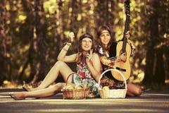 Dos jóvenes forman a muchachas con las cestas de fruta en bosque del verano Fotografía de archivo