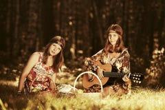 Dos jóvenes forman a muchachas con las cestas de fruta en bosque del verano Fotos de archivo libres de regalías
