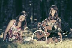 Dos jóvenes forman a muchachas con las cestas de fruta en bosque del verano Foto de archivo