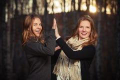 Dos jóvenes forman a muchachas en caminar negro del jersey y de la bufanda al aire libre Imagen de archivo