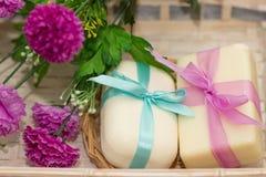 Dos jabones con los arcos en busket de madera con las flores púrpuras Imágenes de archivo libres de regalías