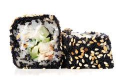 Dos japoneses ajustan los rollos con las huevas negras del tobiko, semillas de sésamo Imagenes de archivo