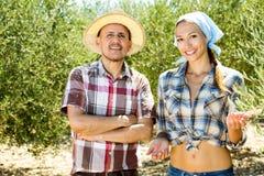 Dos jardineros sonrientes que se unen entre los olivos imagen de archivo libre de regalías