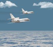 Dos jets privados que vuelan sobre el océano Foto de archivo libre de regalías