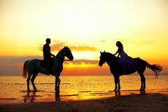 Dos jinetes a caballo en la puesta del sol en la playa Hors del paseo de los amantes Fotografía de archivo libre de regalías