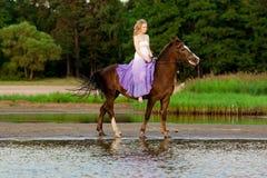 Dos jinetes a caballo en la puesta del sol en la playa Hors del paseo de los amantes Foto de archivo libre de regalías