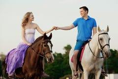 Dos jinetes a caballo en la puesta del sol en la playa Hors del paseo de los amantes Imagen de archivo libre de regalías